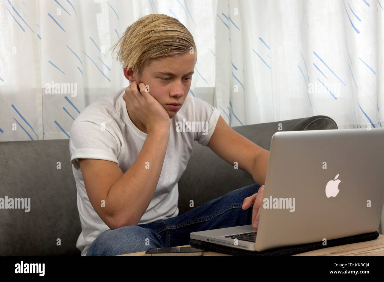 Male teenager on a couch using his Apple MacBook Pro for homework while keeping his friends up-to-date on social - Stock Image