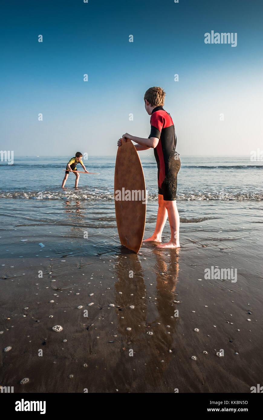 Two boys on a beach skim surfing. Stock Photo