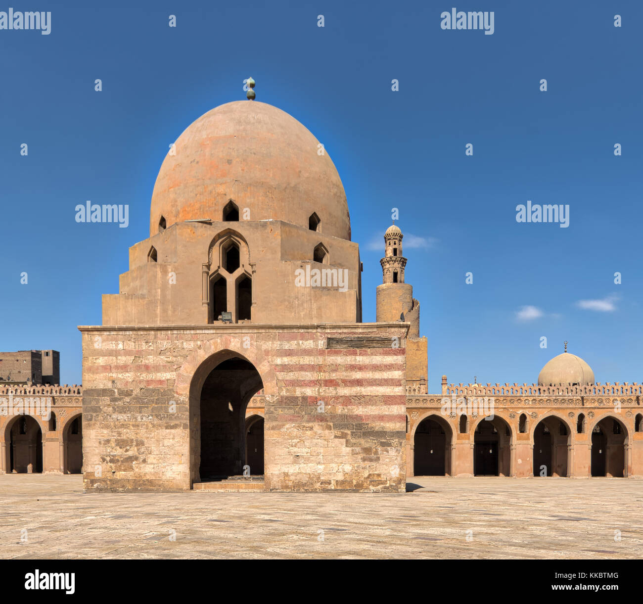 Courtyard of Ibn Tulun Mosque, Cairo, Egypt with ablution fountain and minaret in far distance - Stock Image