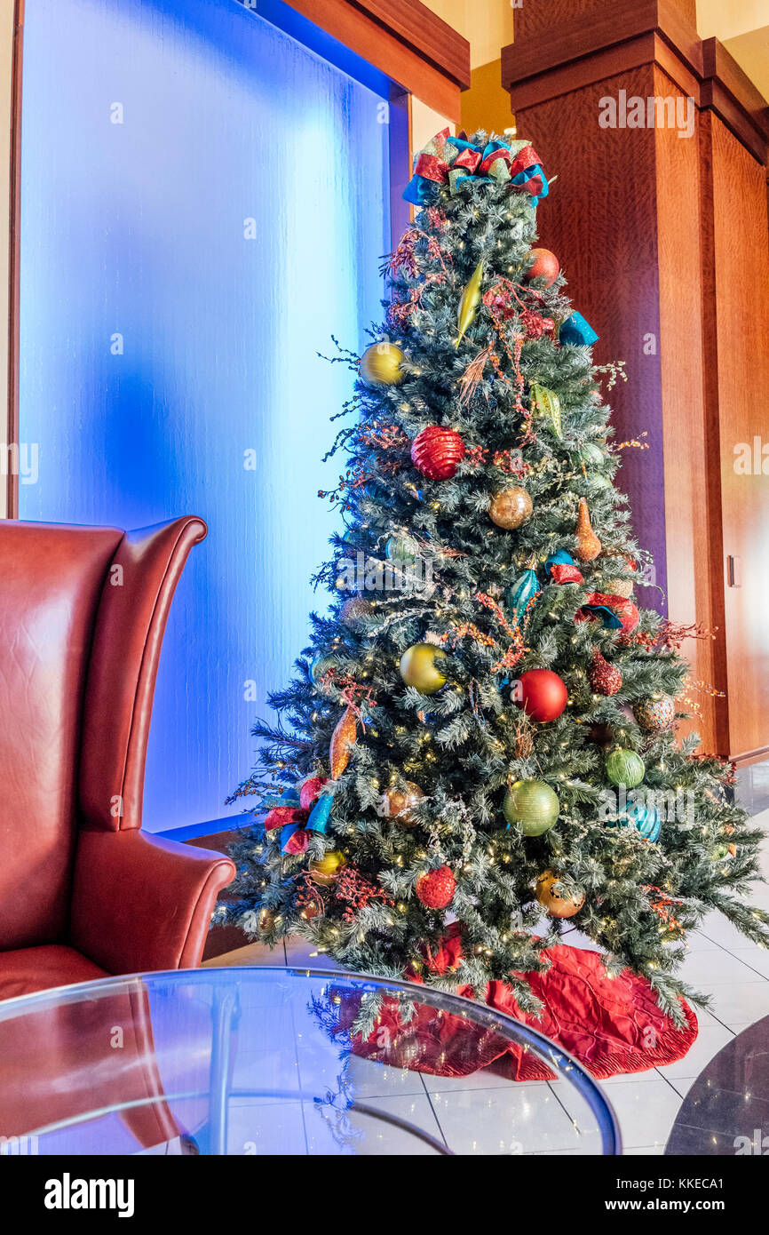 Decorated Christmas tree next to a colorful light panel in the Renaissance hotel lobby, in Montgomery Alabama, USA. - Stock Image