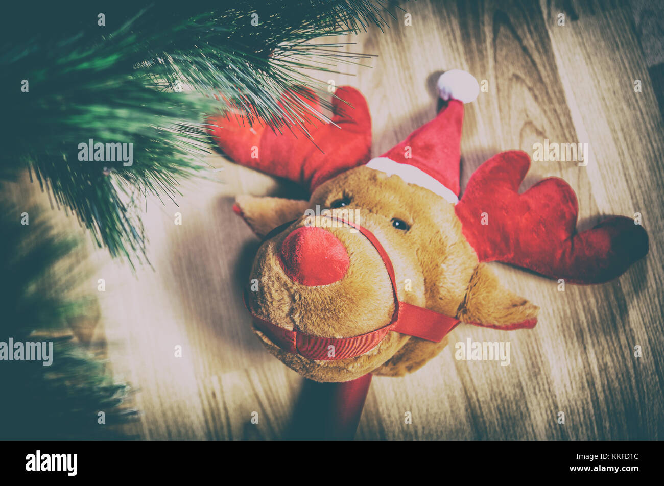 Stick plush reindeer toy over wooden floor close to Christmas Tree at home - Stock Image
