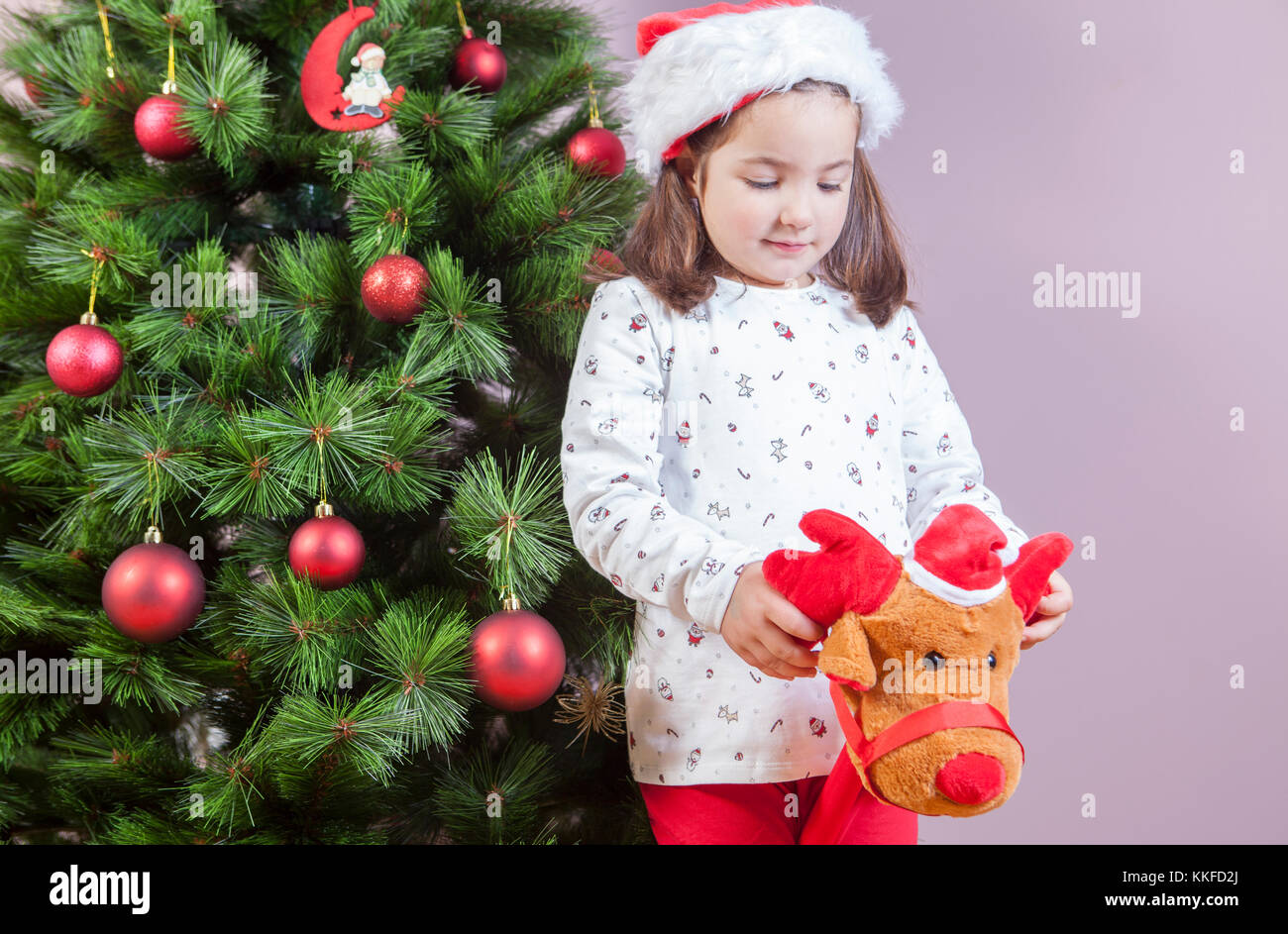 Little child girl playing with stick plush reindeer toy beside Christmas Tree at home - Stock Image