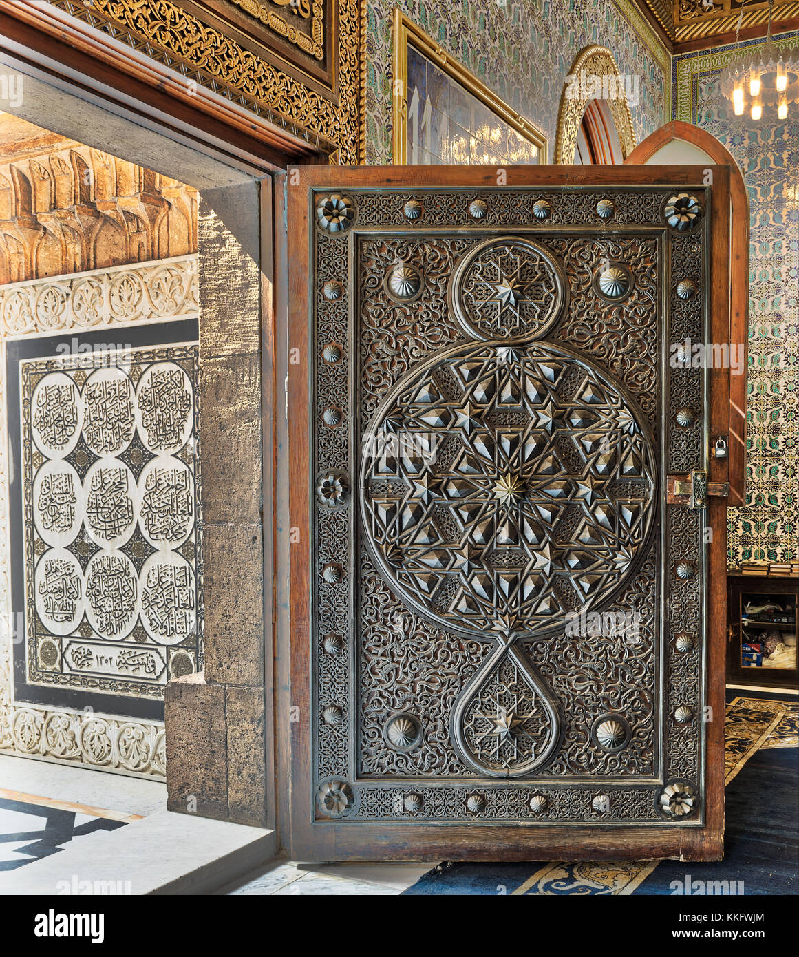 Opened wooden aged door with ornate bronzed floral patterns at the mosque of The Manial Palace of Prince Mohammed - Stock Image