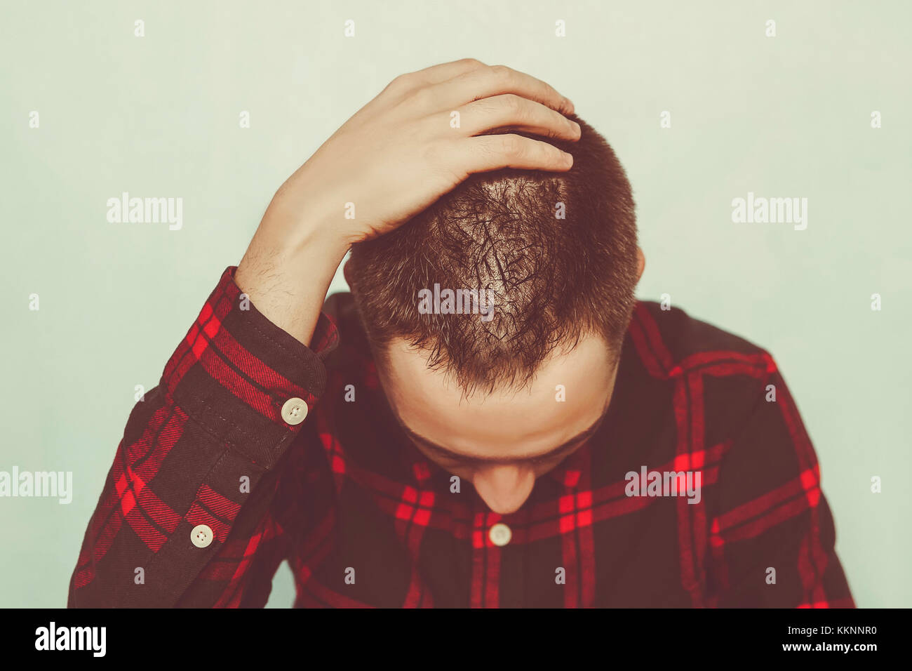 A young man in deep depression. concept of grief. Unrequited love. A man holds a hand to the back of the head. A - Stock Image