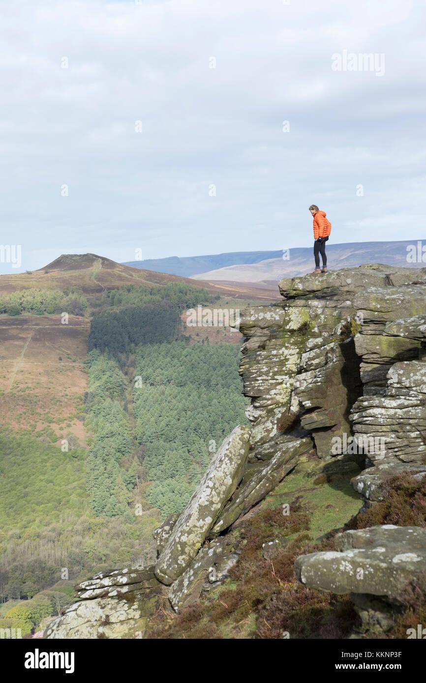 UK, Bamford Edge, walker on the sandstone cliffs along Bamford Edge. - Stock Image
