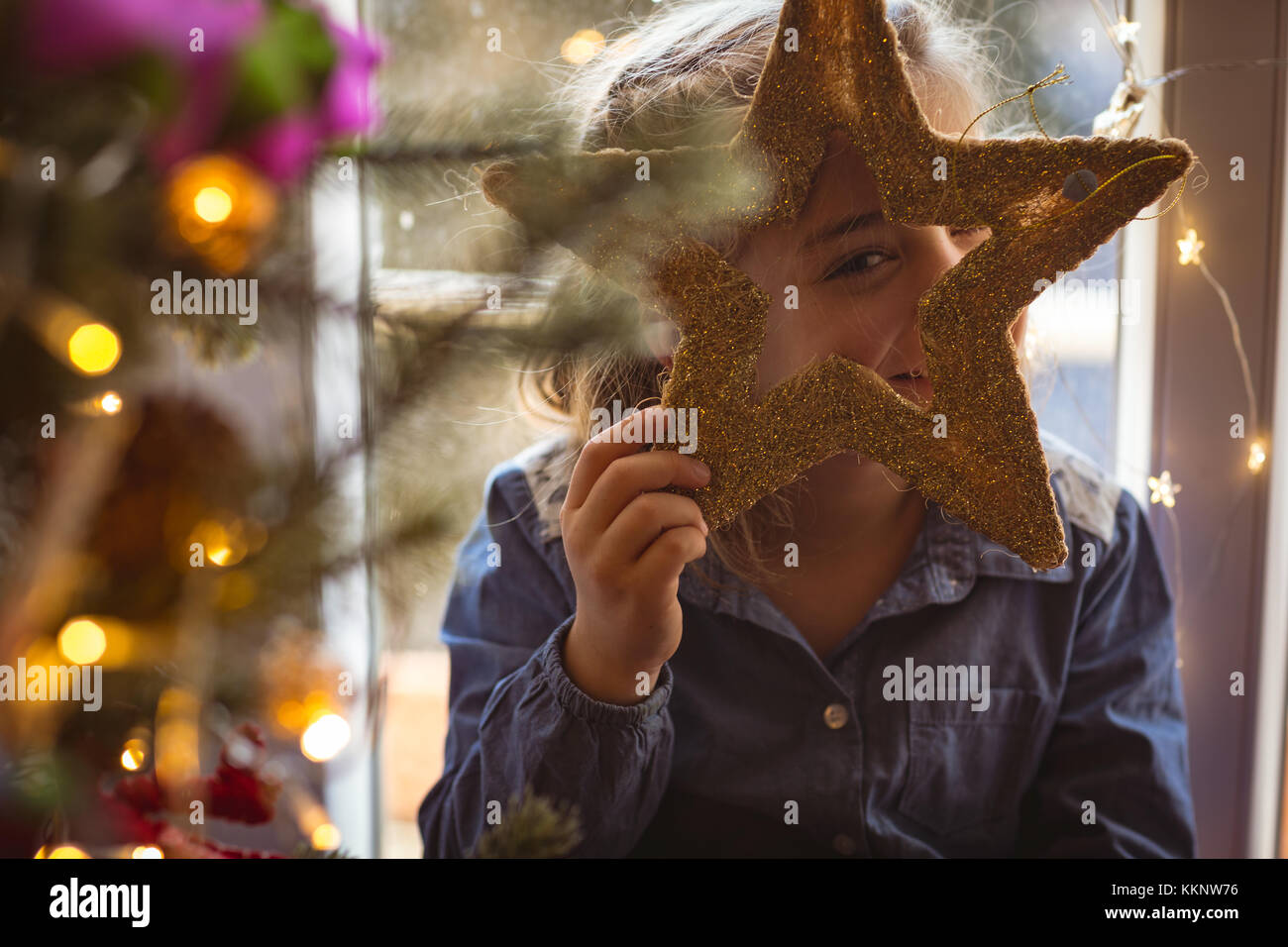 Girl looking standing near christmas tree and looking through star - Stock Image