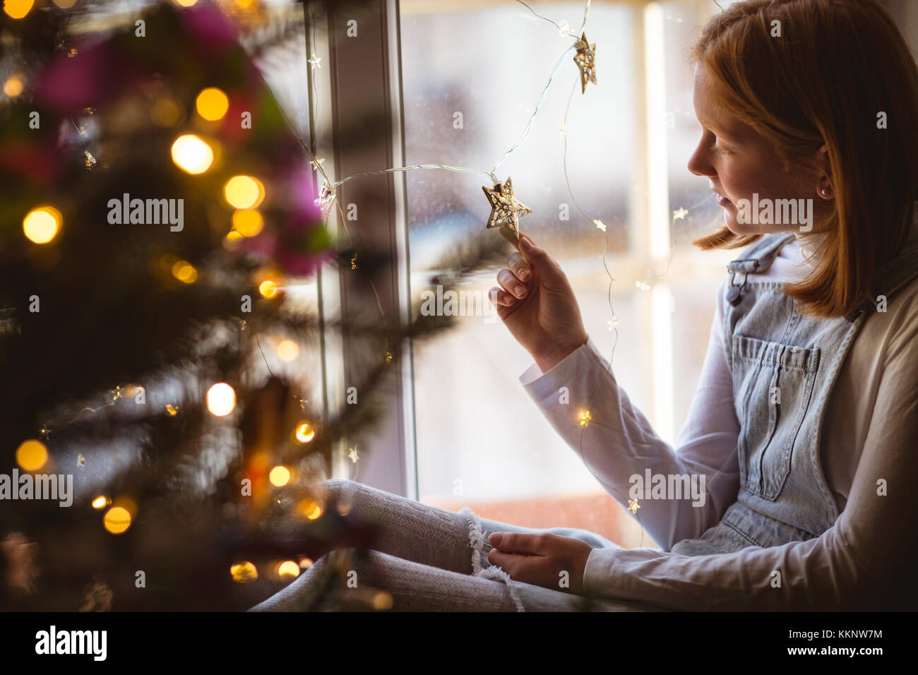 Girl sitting on window sill and looking at star shape - Stock Image