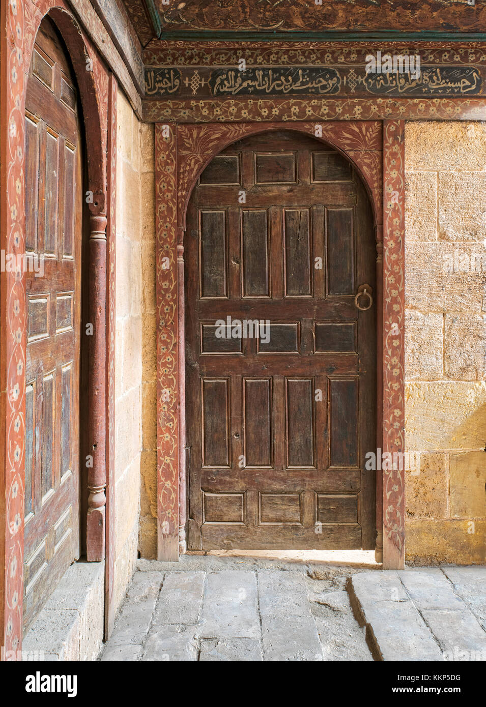 Two wooden aged ornate vaulted perpendicular doors on stone bricks walls, Medieval Cairo, Egypt - Stock Image