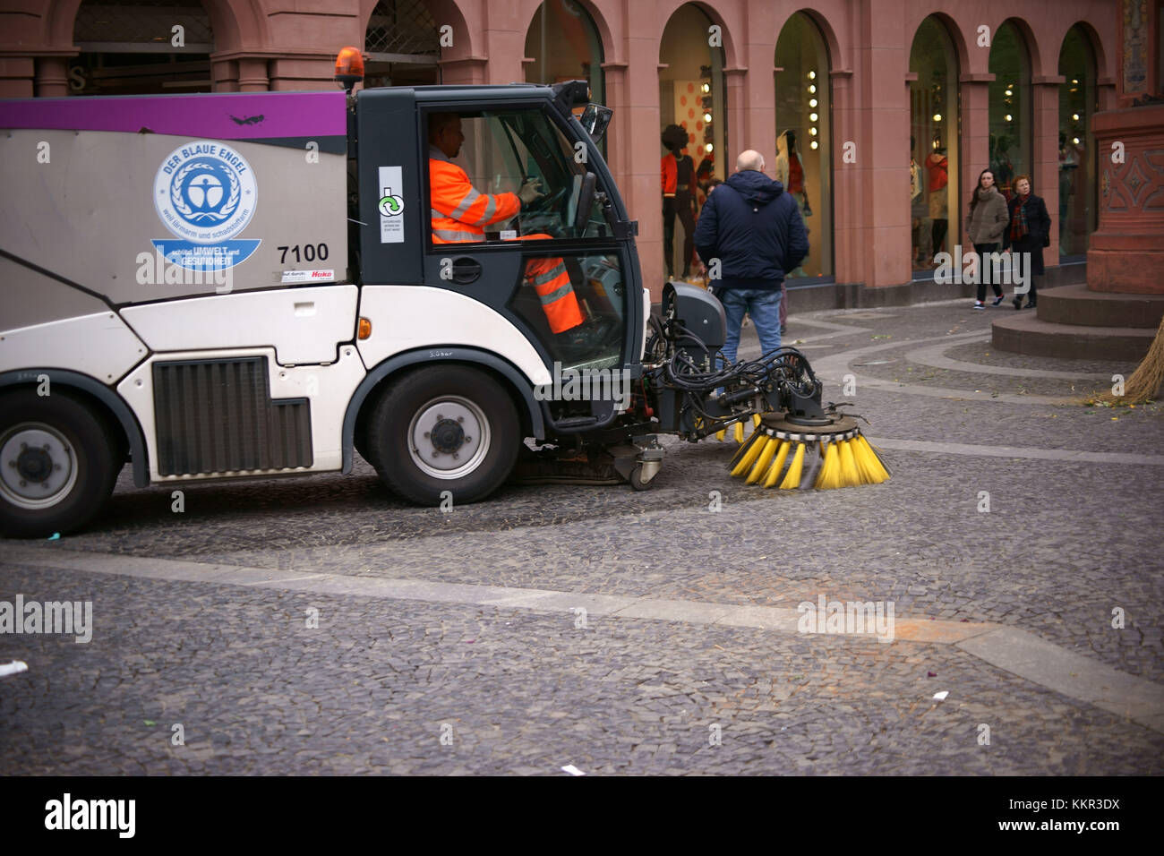 An environmentally friendly street cleaning vehicle cleaning the ground of the marketplace after the weekly market - Stock Image