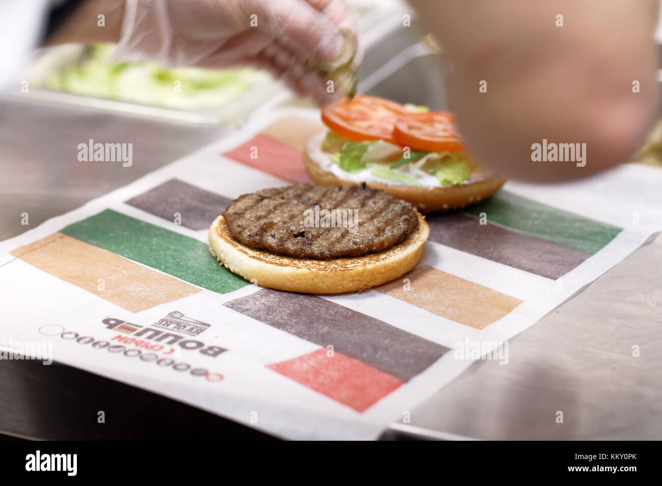 St. Petersburg, Russia - November 29, 2017: Staff preparing a Whopper in 500th Burger King restaurant in Russia - Stock Image