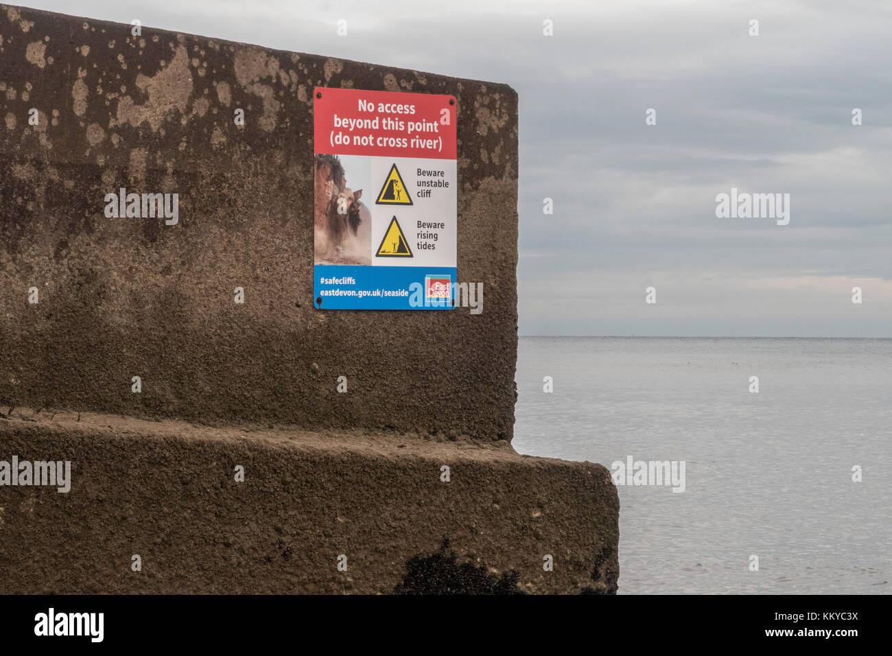 Warning sign on the seafront at Sidmouth, do not cross river, unstable cliff,beware rising tides. - Stock Image