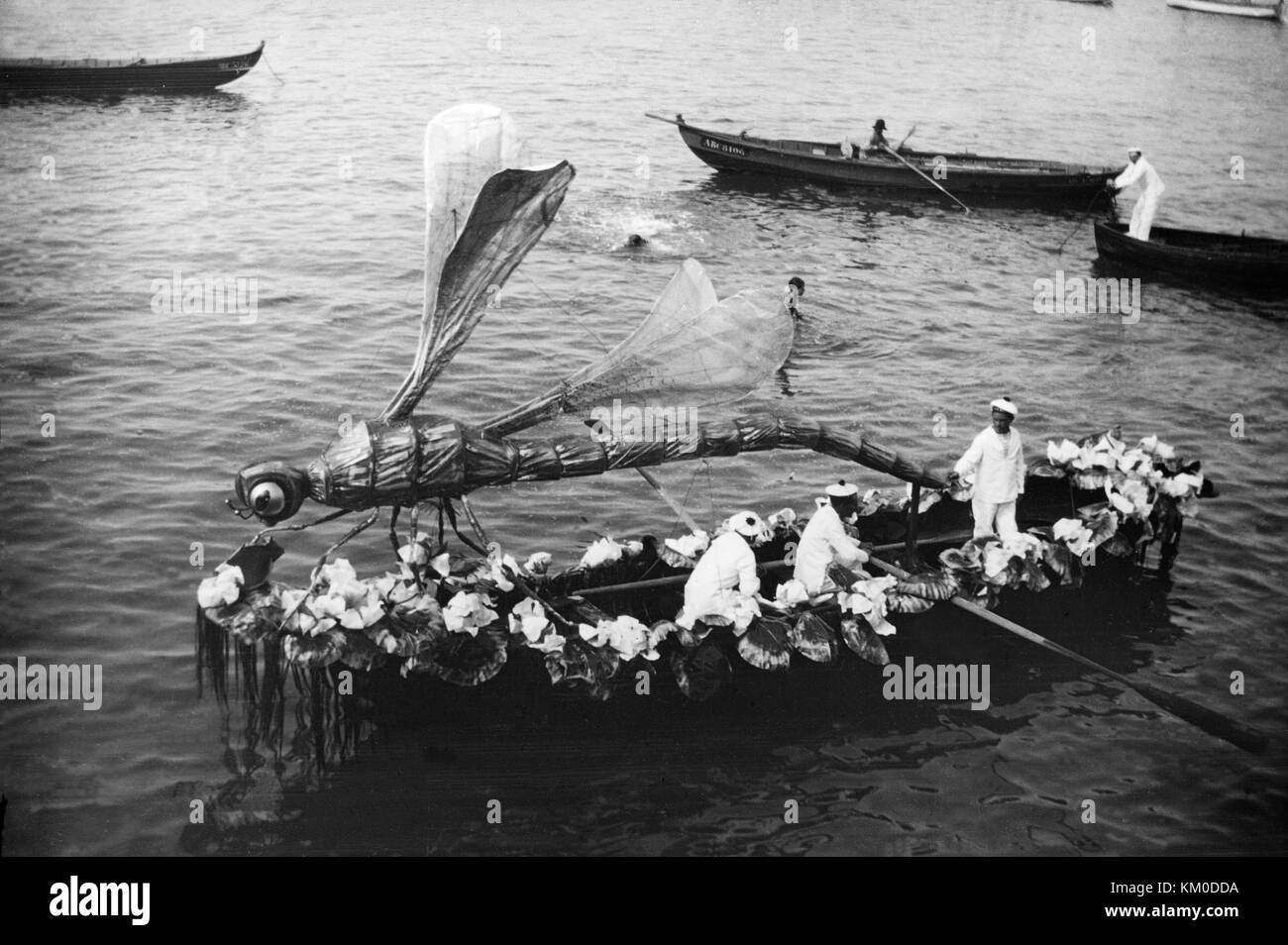 Black and white image taken around the late 19th or early 20th century, showing growing boat in a festival, with - Stock Image