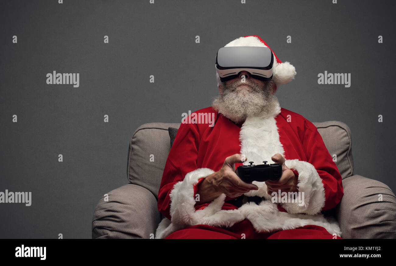 Santa Claus experiencing virtual reality at home and playing videogames using a controller, he is wearing a VR headset - Stock Image