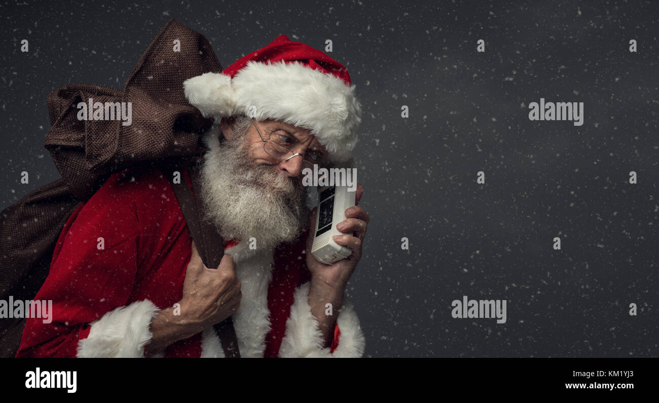 Happy Santa Claus carrying an heavy sack with Christmas gifts and answering phone calls - Stock Image