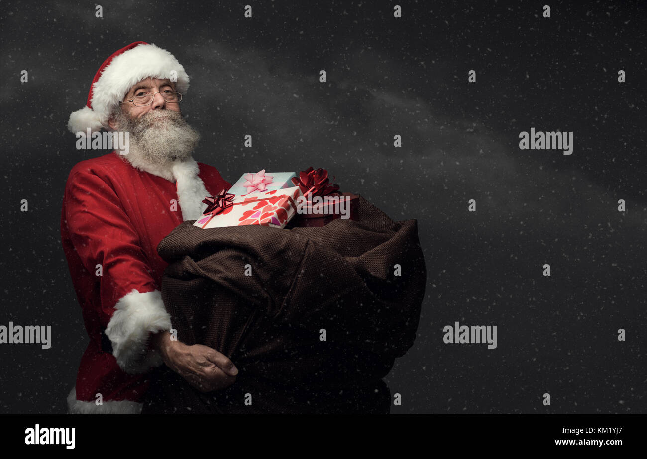 Santa Claus is bringing Christmas gifts in a huge heavy sack, snow falling on the background, holidays and celebrations - Stock Image