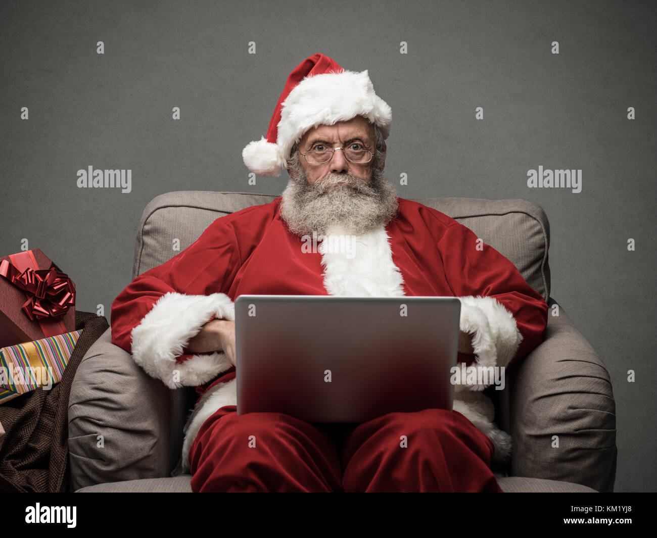 Santa claus relaxing at home and connecting with a laptop, he is chatting and social networking, Christmas time - Stock Image