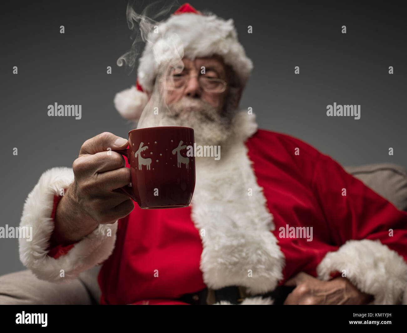 Santa Claus relaxing at home on the armchair and having an hot drink - Stock Image