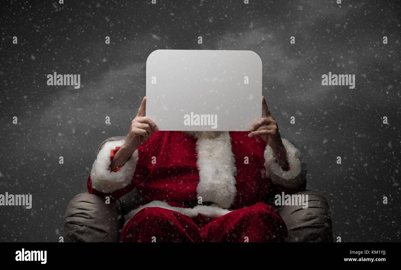 Santa Claus sitting on an armchair and holding a blank sign, Christmas wishes and advertising concept - Stock Image