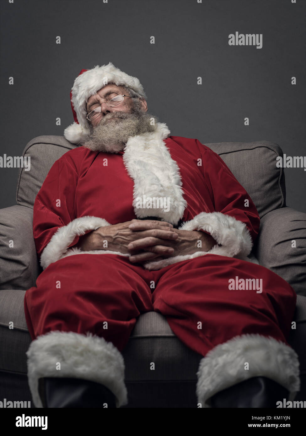 Sleepy Santa Claus taking a nap and relaxing on the armchair on Christmas Eve - Stock Image