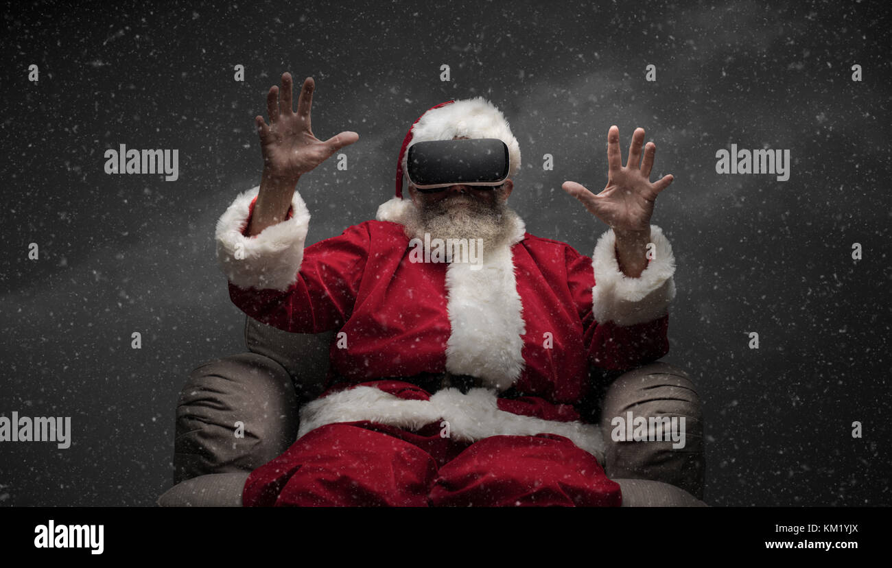 Santa Claus experiencing virtual reality, he is wearing VR glasses and interacting with a virtual environment - Stock Image