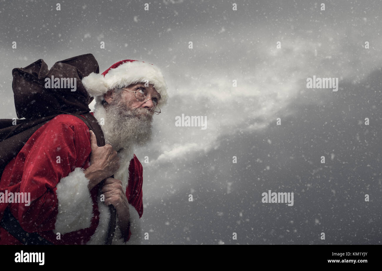 Happy Santa Claus carrying an heavy sack with Christmas gifts, - Stock Image