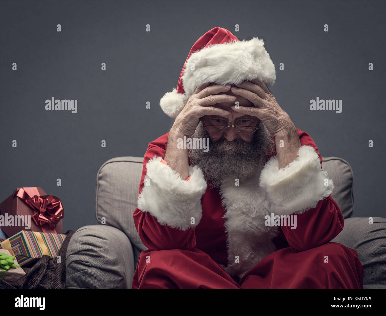 Nervous Santa Claus on Christmas Eve, he is sitting on the armchair with head in hands - Stock Image