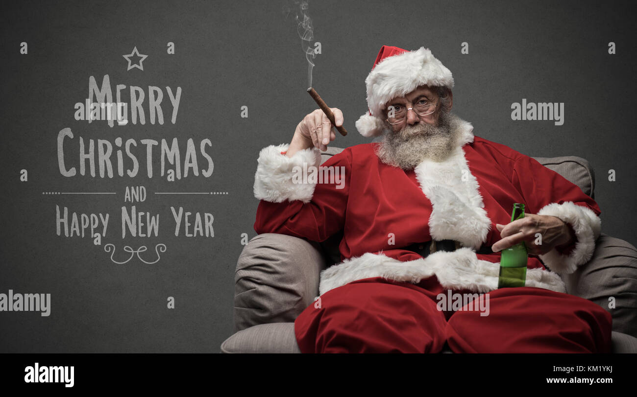 Bad Santa celebrating Christmas at home alone, he is smoking a cigar and drinking beer, Christmas card with wishes - Stock Image