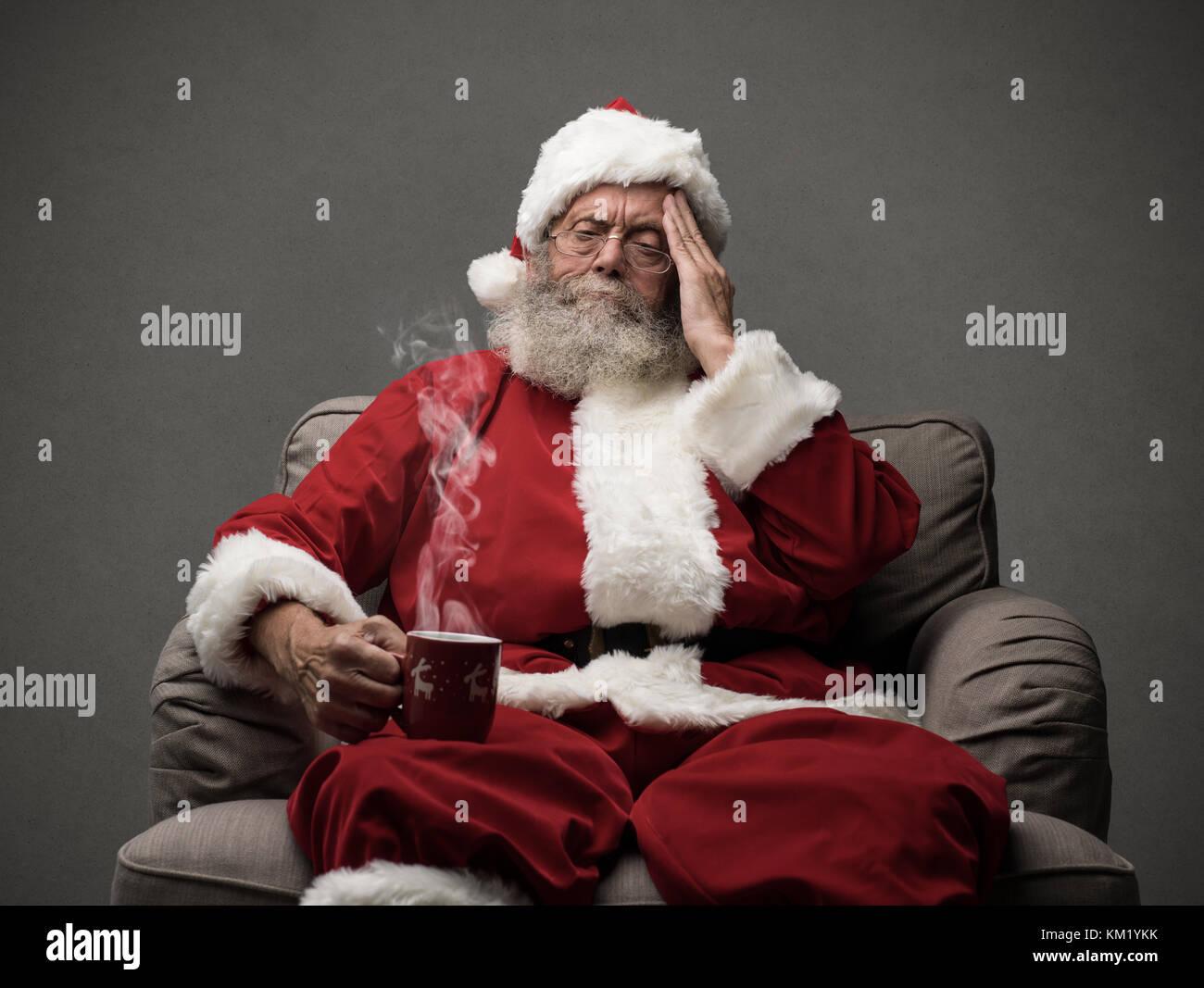 Sad Santa Claus having an headache on Chistmas Eve, stress and illness concept - Stock Image