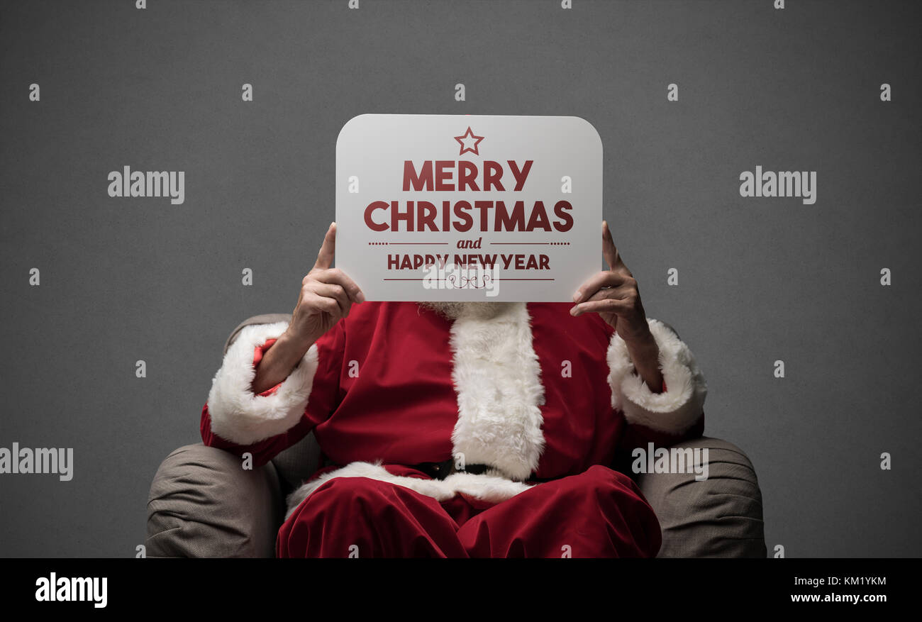 Santa Claus sitting on an armchair and holding a Christmas Card - Stock Image