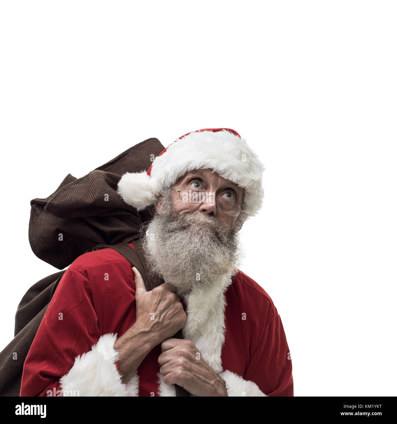 Happy Santa Claus carrying an heavy sack with Christmas gifts, white background - Stock Image