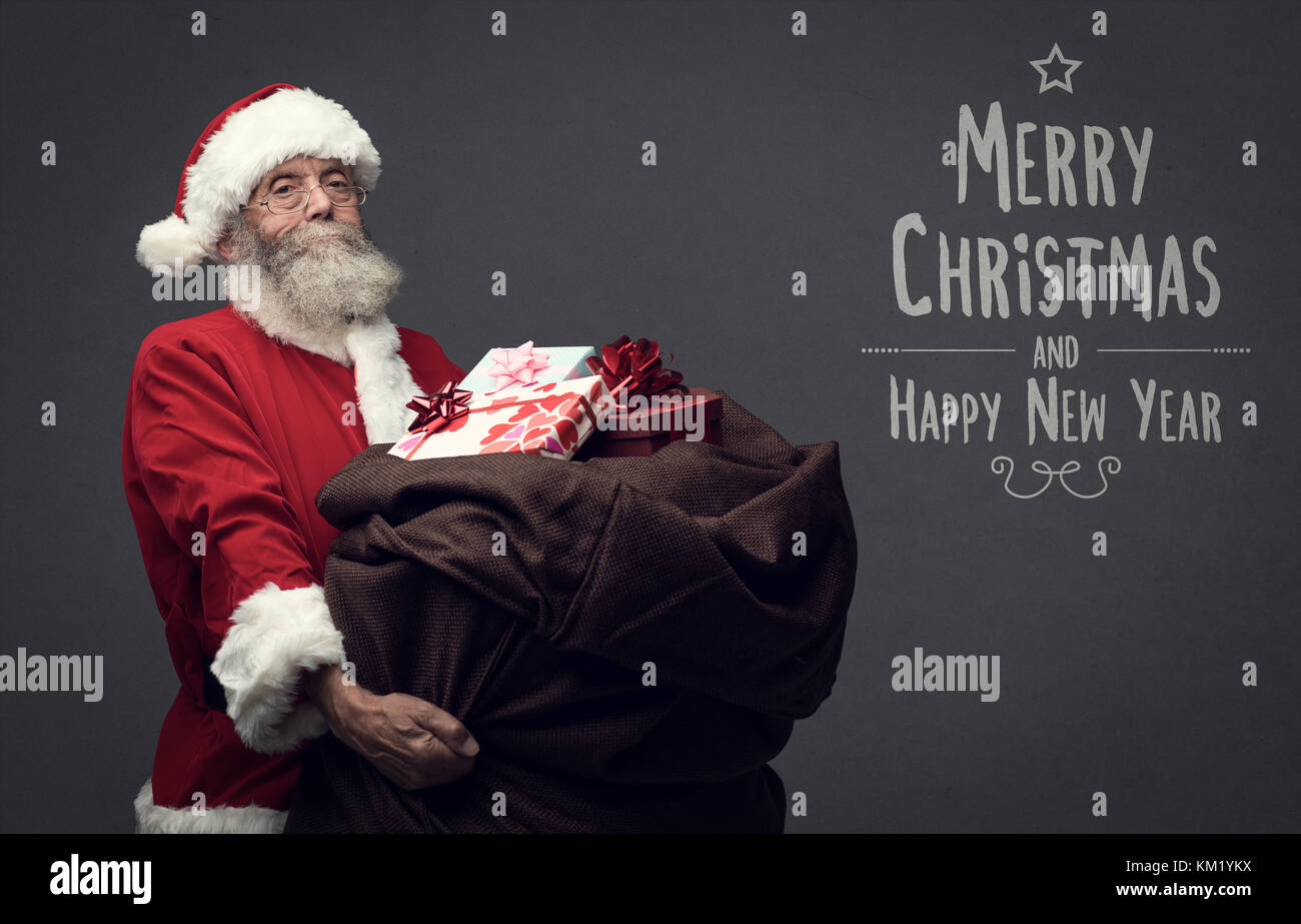 Santa Claus is bringing Christmas gifts in a huge heavy sack, holidays and celebrations concept, Christmas card - Stock Image