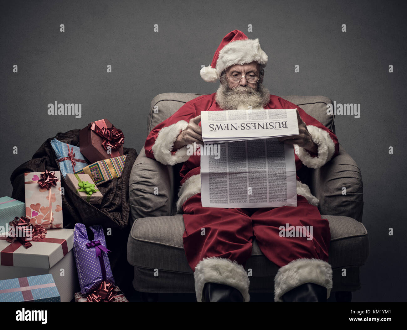 Santa Claus reading business news on a newspaper and relaxing on the armchair at home - Stock Image