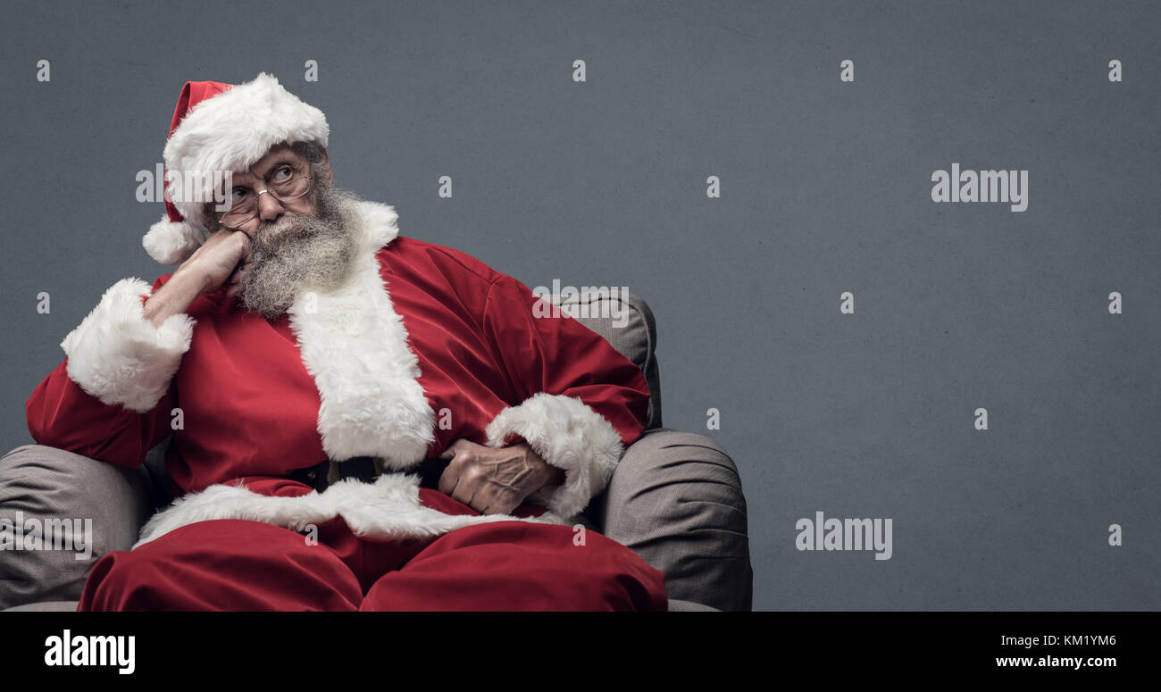 Lazy tired Santa Claus waiting for Christmas, he is sitting on the armchair at home and resting head on hand - Stock Image