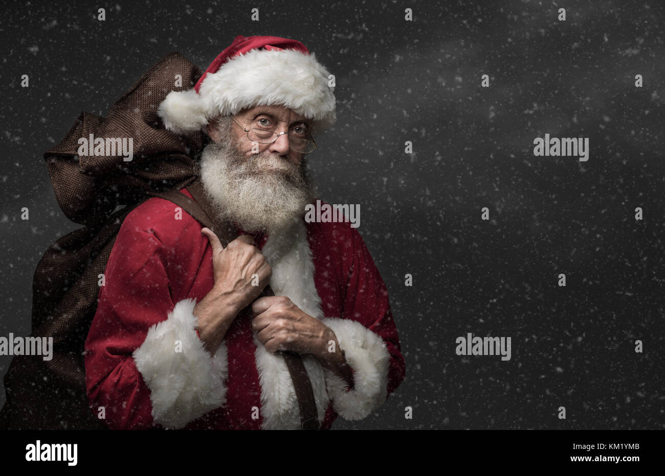 Smiling Santa Claus carrying a sack with gifts on Christmas Eve - Stock Image
