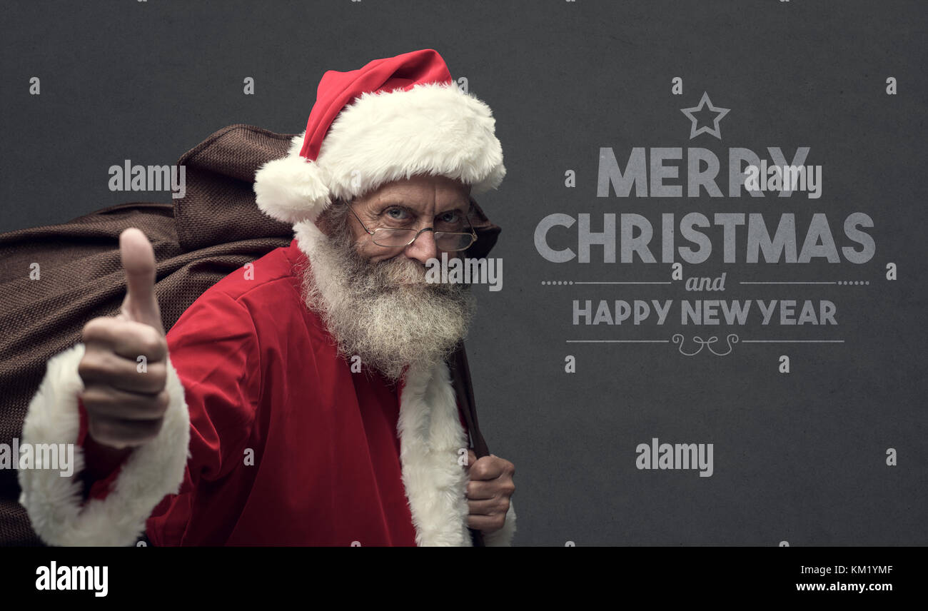 Confident happy Santa Claus giving a thumbs up and carrying Christmas gifts in a huge sack, Christmas card with - Stock Image