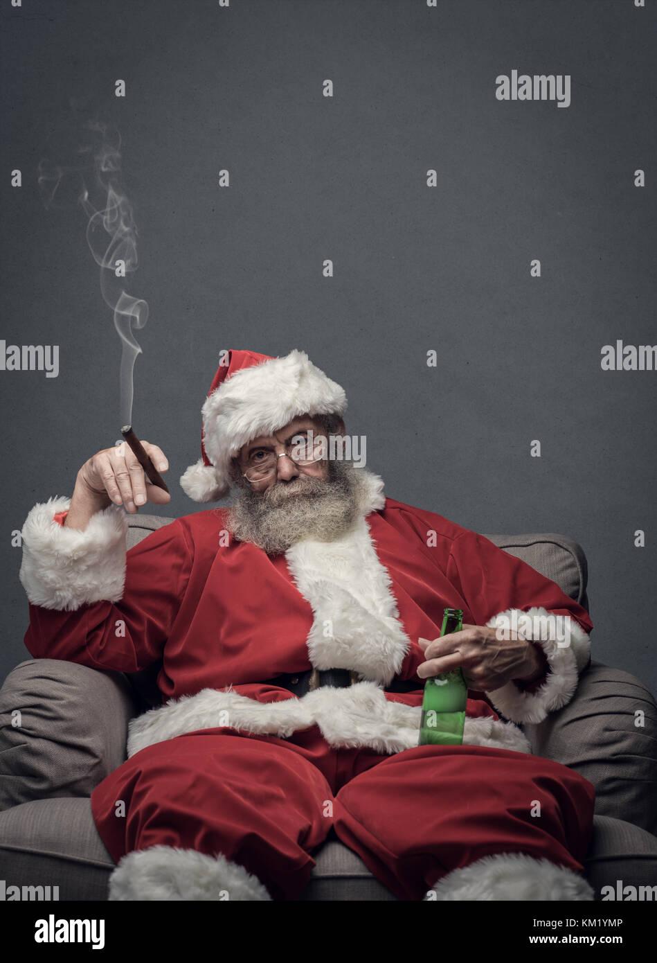 Bad Santa celebrating Christmas at home alone, he is smoking a cigar and drinking beer - Stock Image