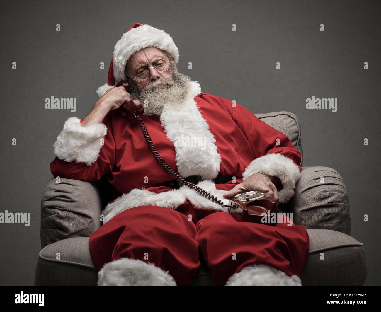 Santa Claus sitting on the armchair and having a phone call, he is holding a receiver and listening - Stock Image