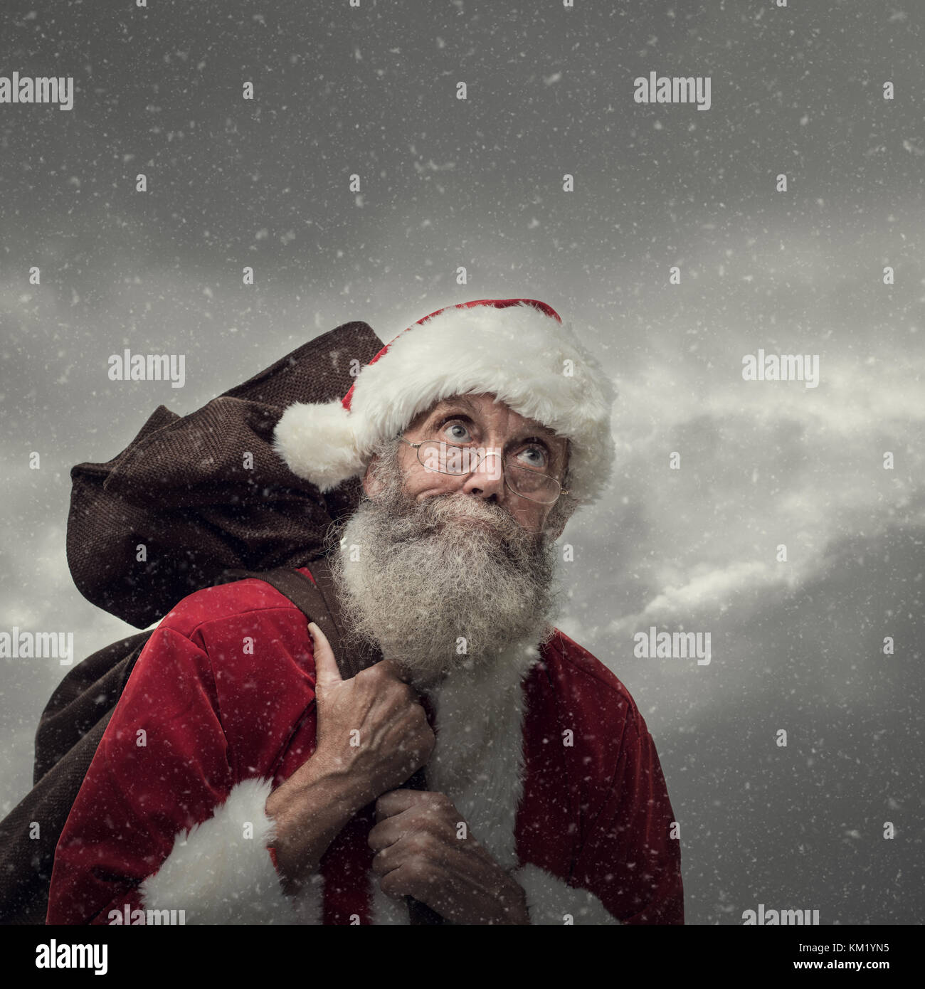 Happy Santa Claus carrying an heavy sack with Christmas gifts - Stock Image