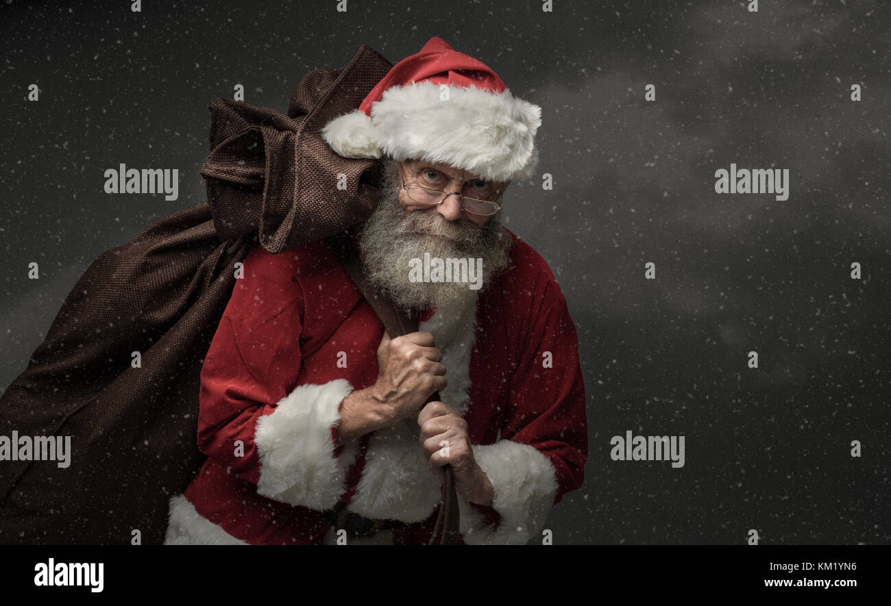 Smiling Santa Claus carrying a sack with gifts on Christmas Eve and snow falling - Stock Image