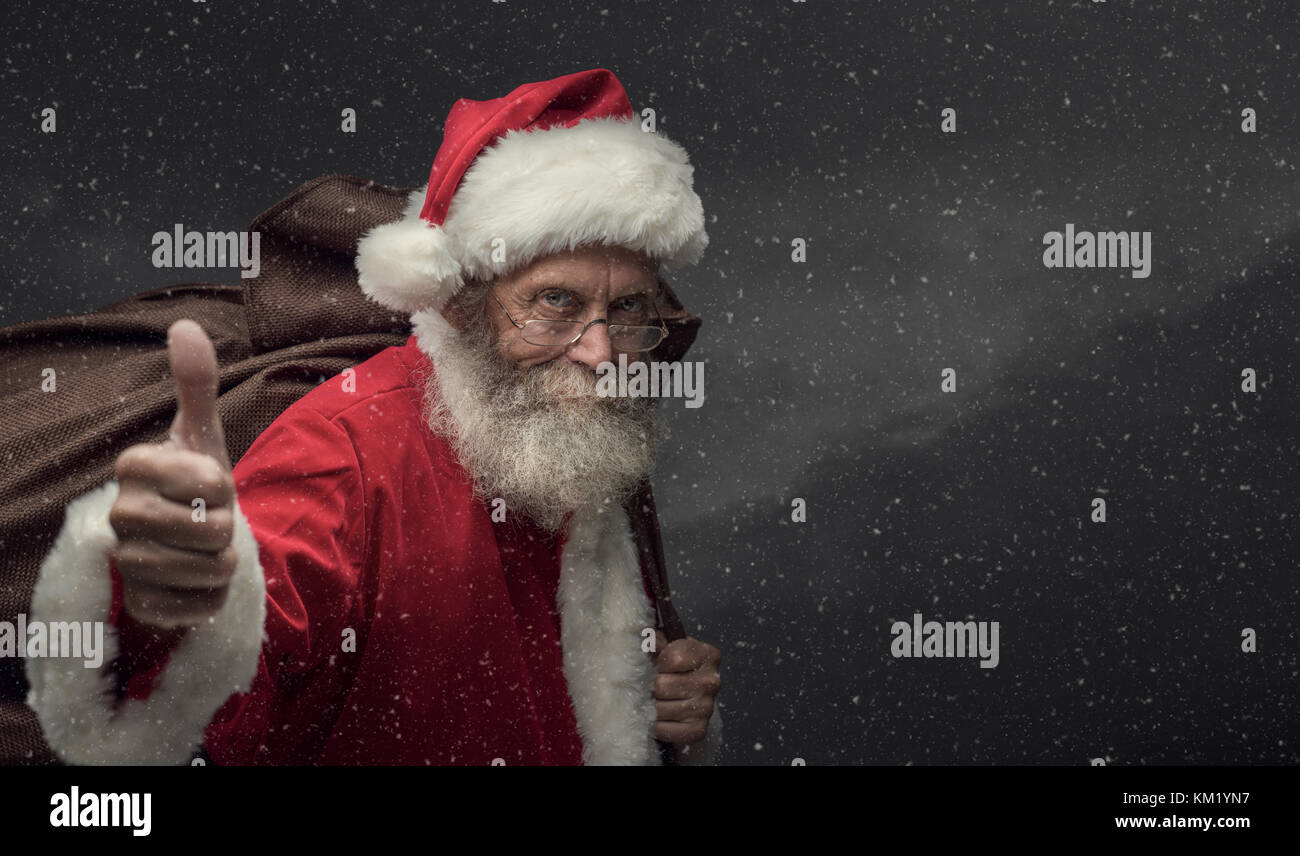 Confident happy Santa Claus under the snow, he is giving a thumbs up and carrying Christmas gifts in a huge sack - Stock Image