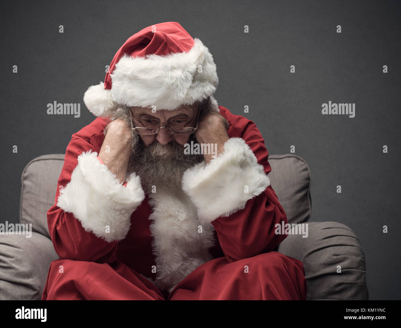 Nervous Santa Claus on Christmas Eve, he is sitting on the armchair and resting head on his hands - Stock Image