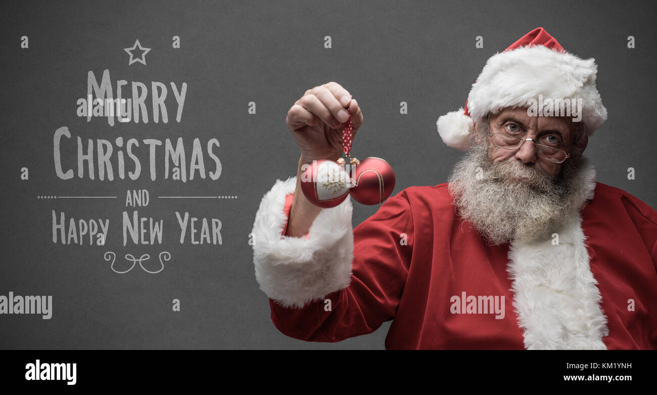 Lazy Santa Claus with sarcastic expression, he is holding two Christmas balls, Christmas card with wishes - Stock Image