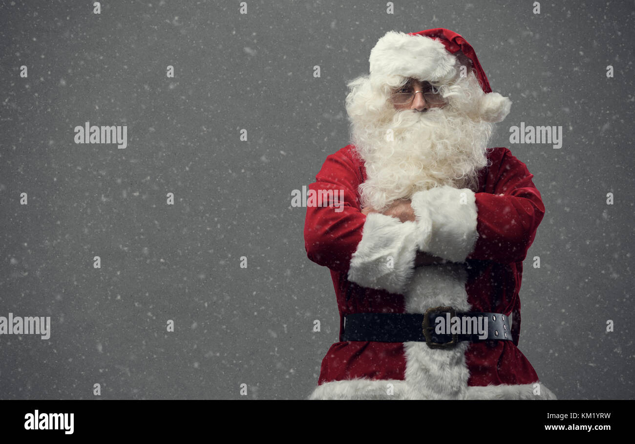 Confident proud Santa Claus posing with arms crossed and looking at camera, snow falling on the background - Stock Image