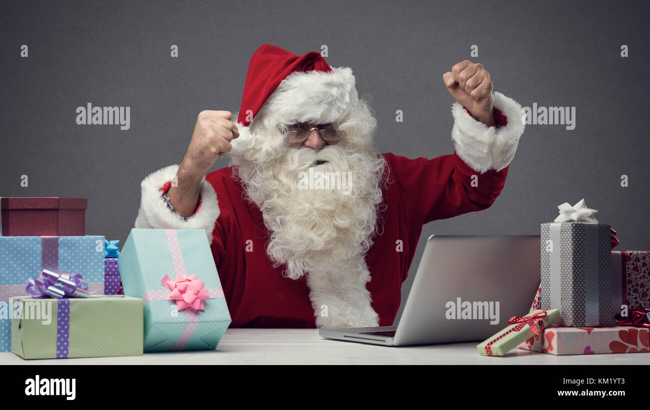 Cheerful winner Santa connecting with his laptop at home, he is celebrating with fists raised - Stock Image