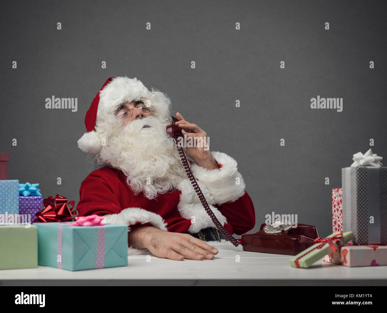 Serene Santa Claus answering phone calls on Christmas Eve and preparing gifts, he is holding the receiver and listening - Stock Image