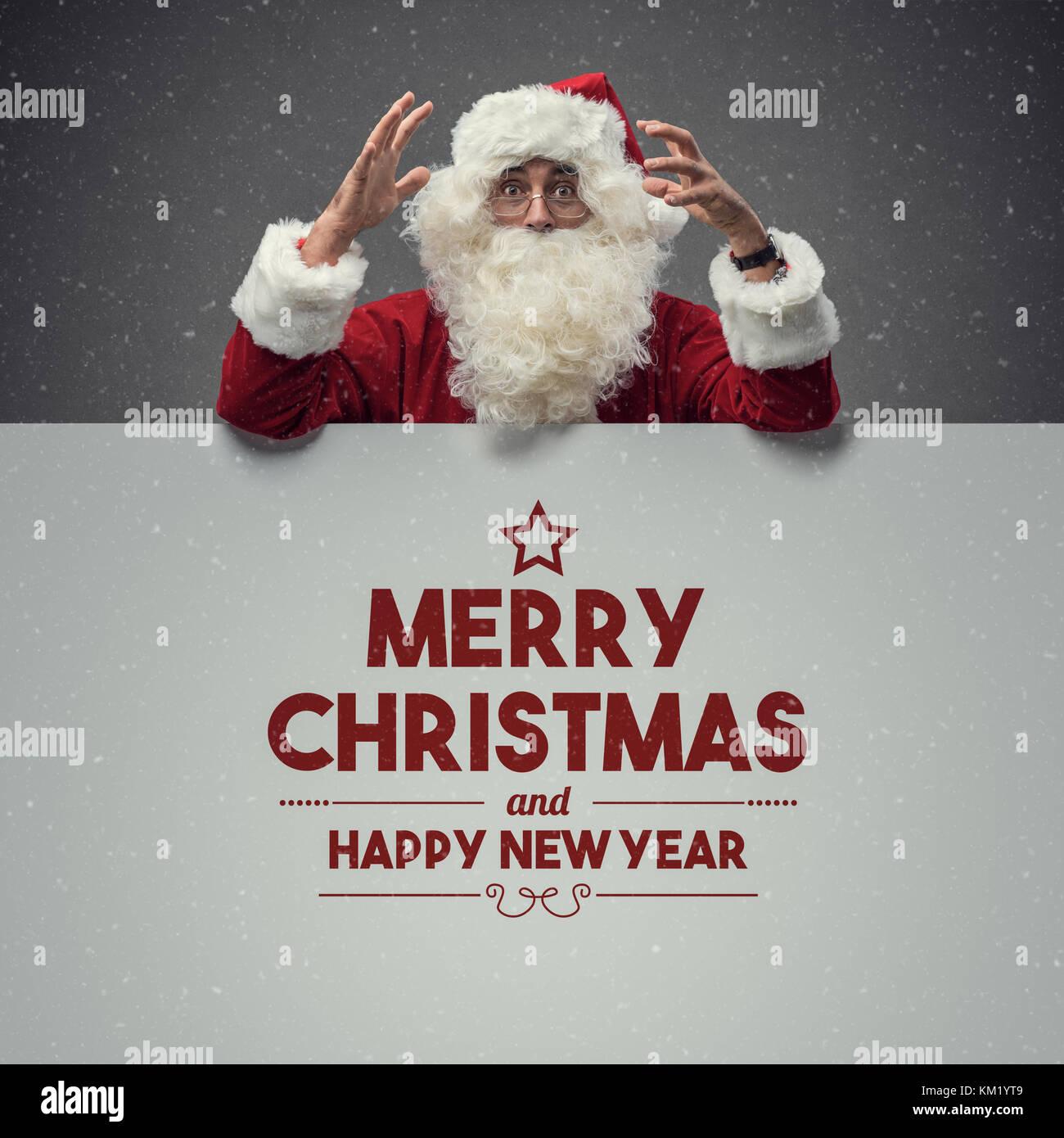 Cheerful happy Santa Claus wishing a joyful merry Christmas and snow falling - Stock Image