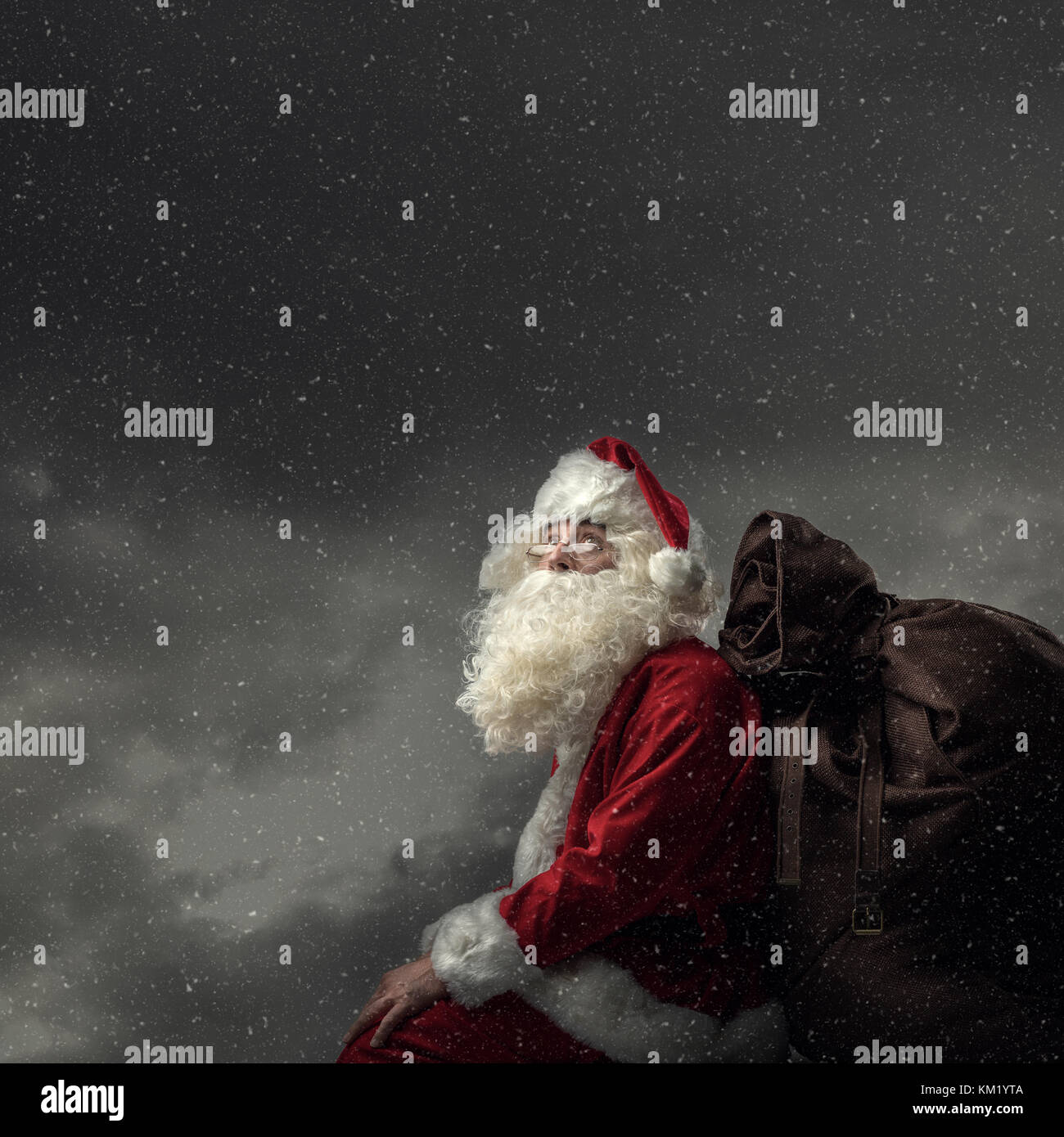 Santa Claus bringing gifts on Christmas Eve: he is sitting on a roof at night, carrying his sack and looking away - Stock Image