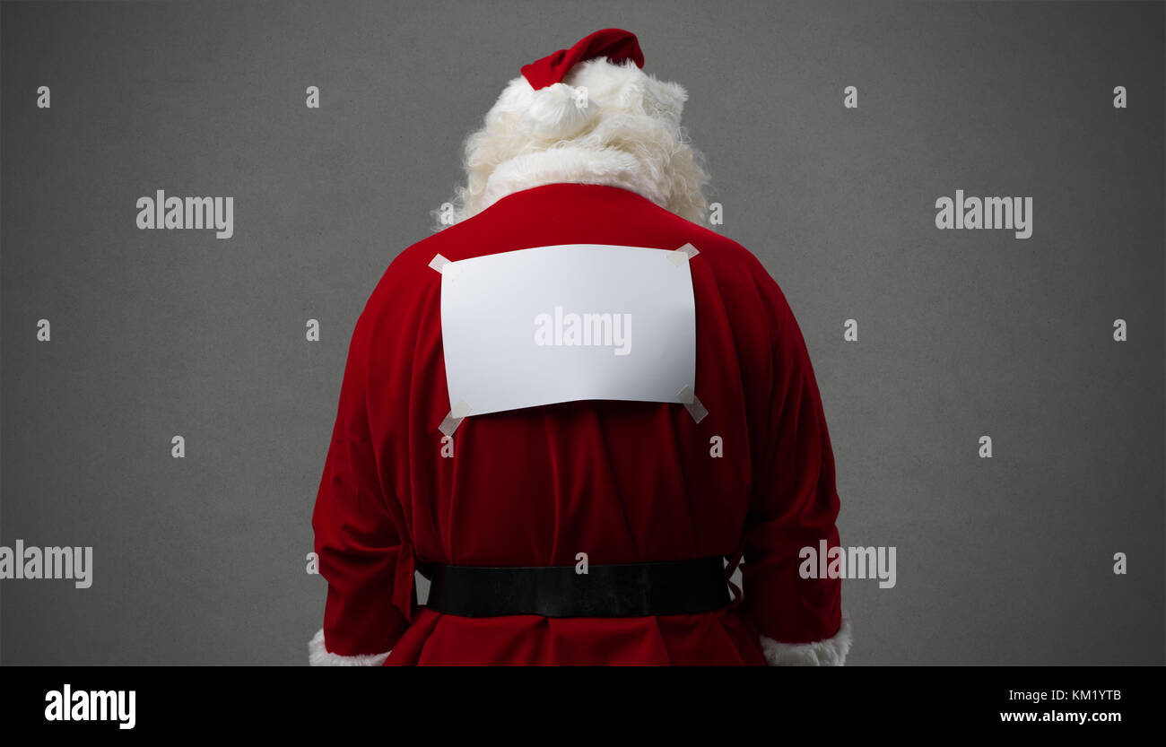 Santa Claus with a blank sign on his back, he is looking down, back view - Stock Image