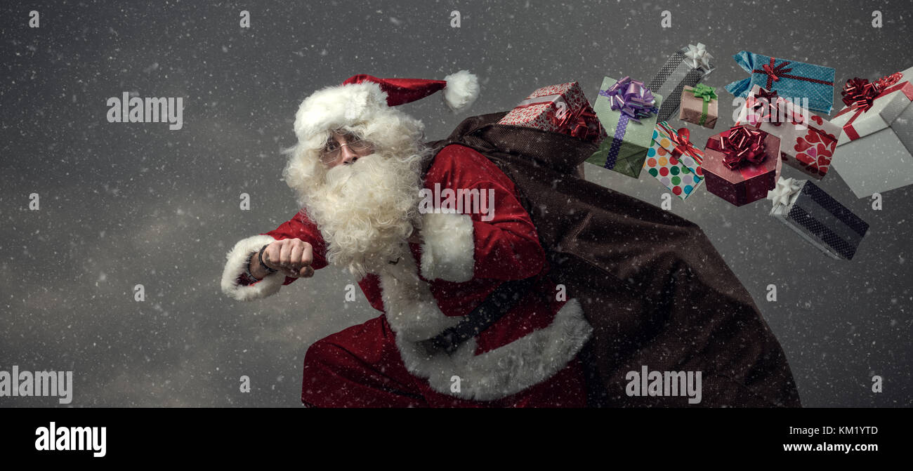 Santa Claus running and delivering presents on Christmas Eve: he is late and losing gifts from his sack - Stock Image