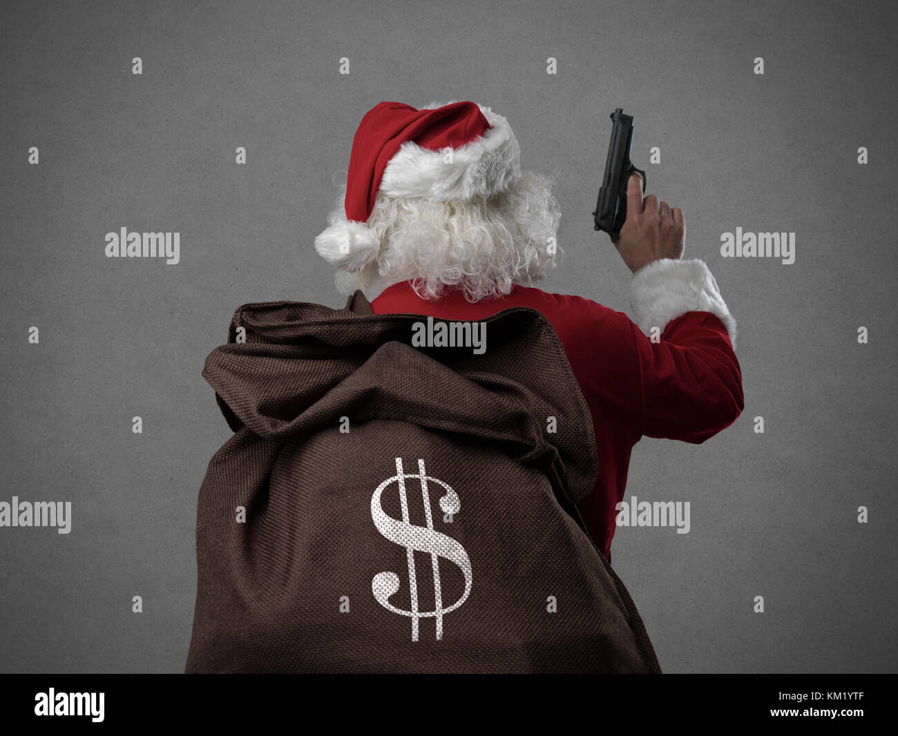 Criminal disguised as Santa Claus holding a gun and carrying a sack full of stolen money, he is robbing houses on - Stock Image